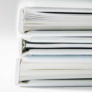 a stack of three white binders full of white paper