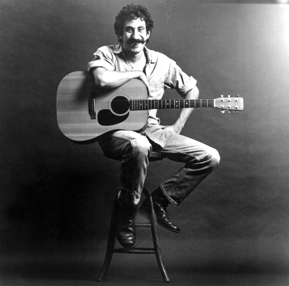 A black and white photo of a mustached man sitting on a stool and resting his arm on a guitar