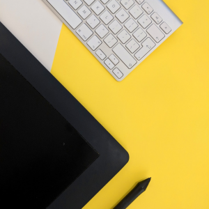 A white keyboard, black tablet, and black stylus pen rest on a yellow background
