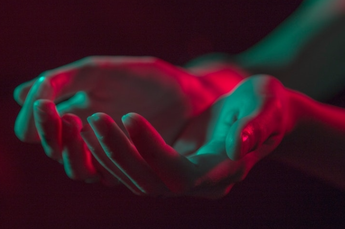 cupped hands in blue and red lighting
