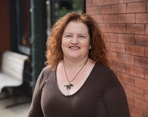 Michelle Anderson, smiling and wearing a brown shirt and horse necklace, stands in front of a brick wall