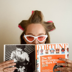woman in curlers and sunglasses reading Fortune magazine