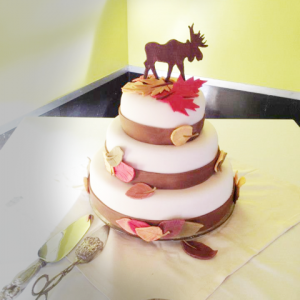 a 3 tiered cake with white fondant and various fall leaves and a moose cake topper