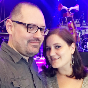 Woman with medium brown hair and man with glasses standing in front of a concert stage