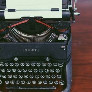 Black manual typewriter with a blank piece of paper loaded in it